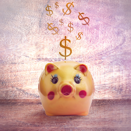 Yellow gold pig bank and falling gold bitcoins on wood table background. Modern earnings and savings concept.