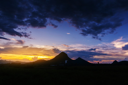 Landscape of beautiful mountains and  sunset with dark cloud. Sunset at wat tham phrathat khao prang and rock buddha statue with mountain, Lop Buri, Thailand.