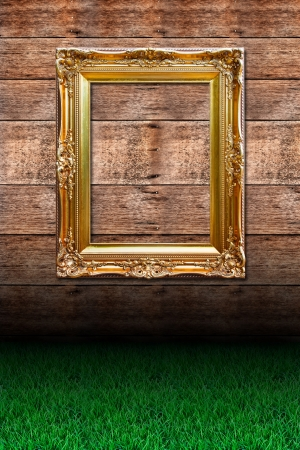 Grass and picture frame against wooden wall photo