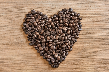 Heart shaped coffee beans with a wooden surface. photo