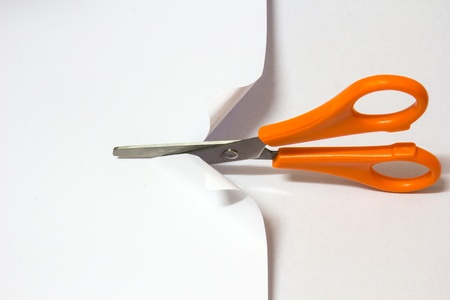 scissors: Yellow scissor cutting white paper on white background