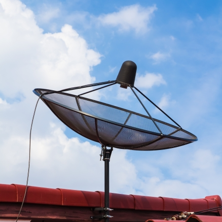housetop: Satellite dish on housetop and blue sky