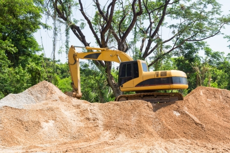 Yellow excavator on mound and green tree  background photo