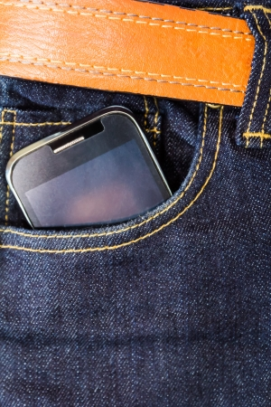 Mobile phone in blue jeans and brown leather belt photo