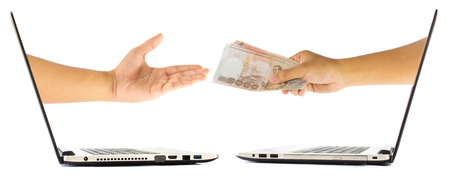 payee: Thai Money in hand grom laptop isolated on white background