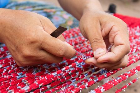 Human working on red Thai silk thread photo