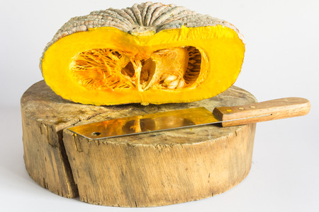 Half on pumpkin with knife and wood block isolated on white background photo