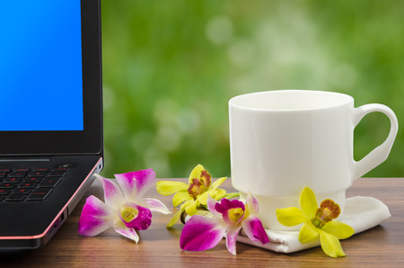White coffee cup with hot coffee and steam and balck laptop computer with blue screen and freh yellow and pink orchid on wooden table in nature bokeh background