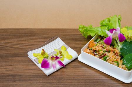 Spicy Salad of Curried Rice ,Yam Naem Khao Thot,Thai food and orchid on wooden table on brown texture background