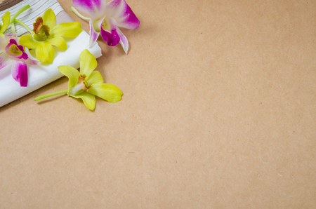 Fresh violet and yellow Orchid on white hankerchief on brown texture background with blank space for text