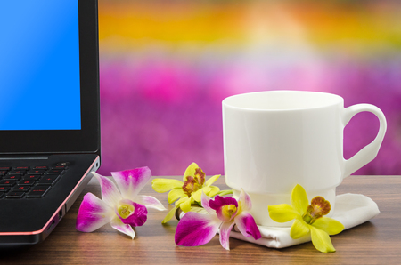 hanky: White coffee cup with hot coffee and steam and balck laptop computer with blue screen and freh yellow and pink orchid on wooden table in beautiful flower garden nature bokeh background