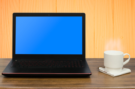 hankerchief: Black large display laptop computer and hot coffee with steam in white coffee cup on white hankerchief on wooden table in wooden texture room background