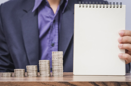 copyspace: Businessman show blank pager paper notebook with copyspace and growing money coin on wooden table in the office. Business and money concept