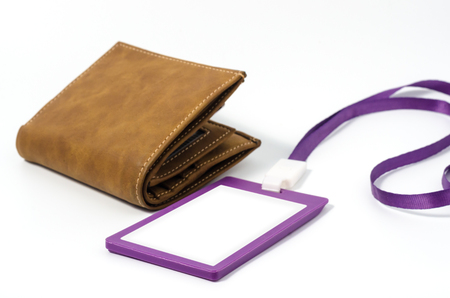 Purple lanyard and plastic badge with blank space mock up isolated and brown leather wallet on white background