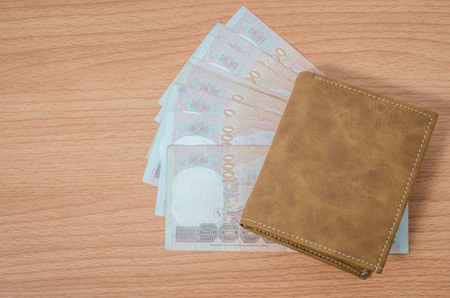 Thai money in brown leather wallet on wooden texture background