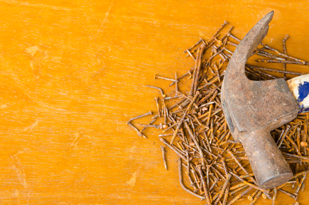 Rusted nail in rusted hammer head and group of rusted nails in brown wooden texture background