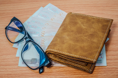 leather texture: Thai money in brown leather wallet and black spectacle eyeglasses on wooden texture background Stock Photo