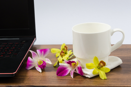White coffee cup, black laptop computer and fresh yellow and pink orchid on wooden table in white background
