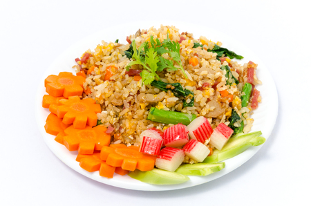 Fried rice with crap sticks, carrots, and cucumber slices on white plastic dish isolated on white background