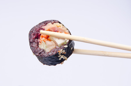 Japanese sushi with black rice and vegetable in chopsticks in human hand isolated on white background Reklamní fotografie