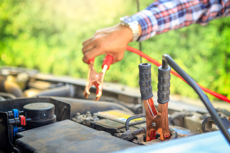 Close up hand of car technician holding cable to connect to battery,Car mechanic uses battery jumper cables charge a dead battery,A car mechanic uses battery jumper cables transferring power,spot focus. Stock fotó