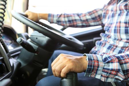 El conductor del camión sigue conduciendo con una mano y cambia de marcha, el hombre detrás del volante del camión, enfoque en el punto.