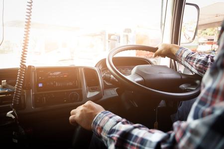 Vrachtwagenchauffeur blijft met één hand rijden en verandert van versnelling, de man achter het stuur van de semi-vrachtwagen, spotfocus. Stockfoto