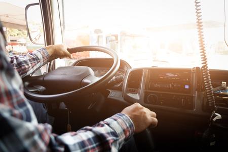 L'autista del camion continua a guidare con una mano e cambia marcia, l'uomo dietro il volante del semirimorchio, messa a fuoco spot.