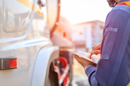 Autisti di camion mano che tiene tablet che controlla l'elenco dei prodotti, autista che scrive libri di bordo elettronici, messa a fuoco spot.