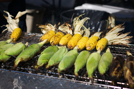 Grilled sweet corn on hot stove in a hot summer street fair.