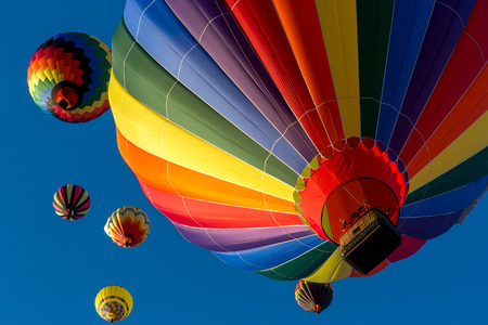 Colorful hot air balloons flying in the bright blue sky at the Festival of Ballooning in New Jersey. Stock Photo