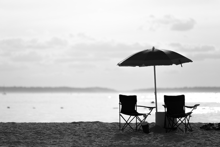 Black and white of lounge chairs and umbrella on the beach in a hot summer day. Stok Fotoğraf