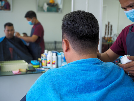 man getting haircut at barber shop. Hairdresser cutting hair of customer at salon. Reklamní fotografie