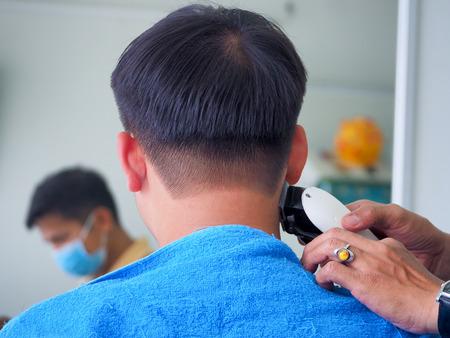 man getting haircut at barber shop. Hairdresser cutting hair of customer at salon. Reklamní fotografie - 98482048