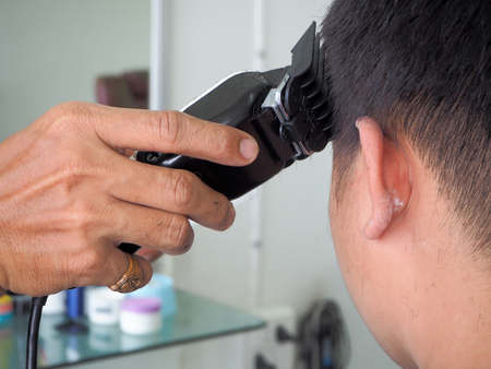 man getting haircut at barber shop. Hairdresser cutting hair of customer at salon. Stockfoto