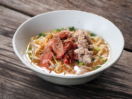 Closeup of hot noodles. Thai local noodle. Thai style pork spicy noodle soup. Pork noodle spicy soup ,Thai noodle,Tom yum. Bowl With spoon and chopsticks on wooden table. Stockfoto