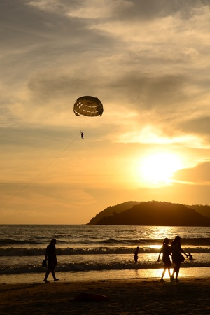 Silhouette of a parasailor at sunset Stock Photo