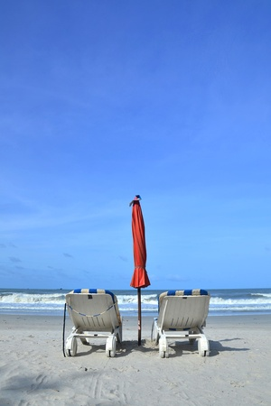 Two beach chairs on white sandy tropical beach