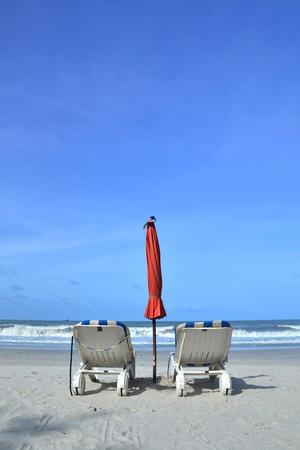 Two beach chairs on white sandy tropical beach