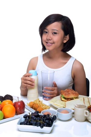 An attractive Asian woman eating a healthy breakfast