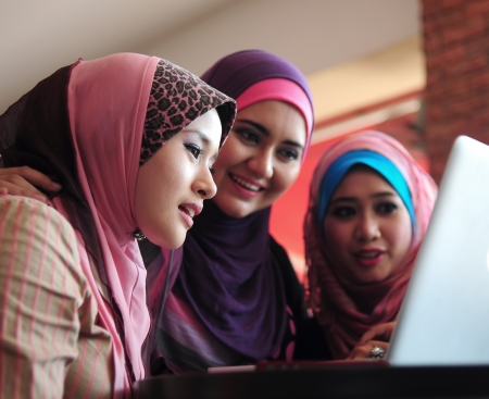 malay: young muslim woman in head scarf using laptop in cafe with friends Stock Photo