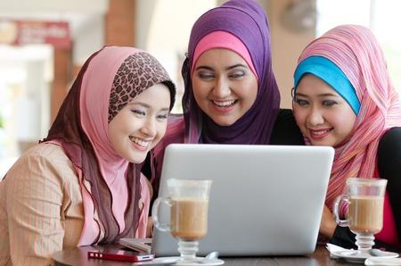 femme musulmane: jeune femme musulmane en foulard sur la t�te en utilisant un ordinateur portable dans un caf� avec des amis