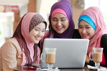 young muslim woman in head scarf using laptop in cafe with friends photo