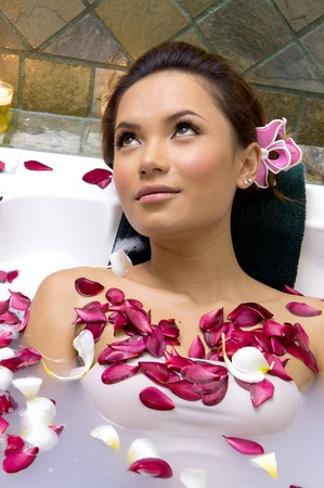 Woman relaxing in bath with plumeria petal photo