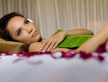 Woman relaxing during beauty and spa treatment with plumeria petal