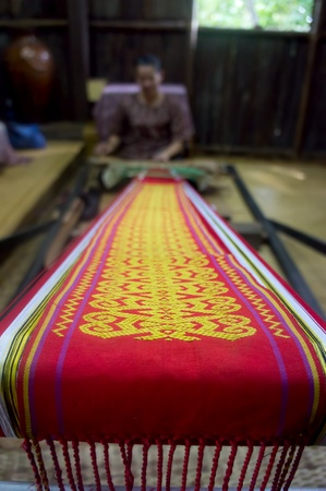KUCHING, SARAWAK, MALAYSIA - FEB 25: The ethnic Iban lady of Borneo weaving an exquisite decorative cloth in Kuching, Sarawak, on February 25, 2012.