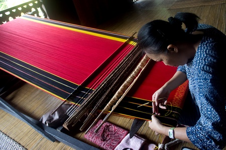 KUCHING, SARAWAK, MALAYSIA - FEB 25: The ethnic Iban lady of Borneo weaving an exquisite decorative cloth in Kuching, Sarawak, on February 25, 2012. Editorial
