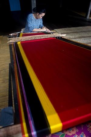 KUCHING, SARAWAK, MALAYSIA - FEB 25: The ethnic Iban lady of Borneo weaving an exquisite decorative cloth in Kuching, Sarawak, on February 25, 2012. Editorial