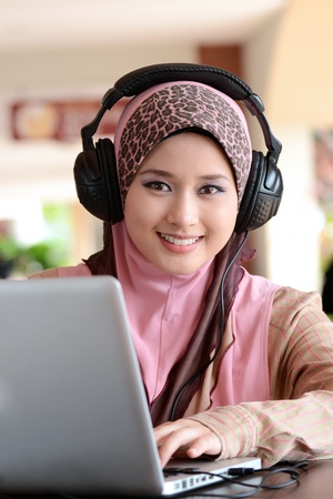 Young pretty Asian muslim woman in head scarf listens to audio with headphone while working on laptop in cafe photo