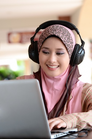 arab people: Young pretty Asian muslim woman in head scarf listens to audio with headphone while working on laptop in cafe